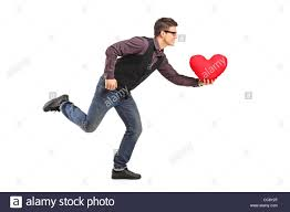 Man Shaped Pillow A Young Man Running With A Red Heart Shaped Pillow In His Hand