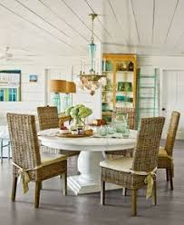 beach style dining room with round white table and wicker parsons chairs beach style dining room beach dining room design beach dining room ideas dining