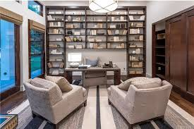a home office. A Home Office Exists In The House, Featuring Huge Bookshelf And Glass Doors Windows. Flushmount Lighting Illuminates Room.