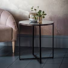 round metal based side table with an aged bronze finish with a smoked mirror top