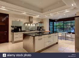 Image Modern Down Lighting On False Ceiling In Modern Spanish Kitchen With Stainless Steel Island Unit And White Ceramic Tiled Floor Alamy Down Lighting On False Ceiling In Modern Spanish Kitchen With Stock