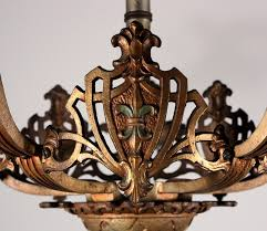 a wonderful antique iron and brass semi flush mount chandelier dating from the 1920 s this tudor chandelier features a fabulous fleur de lis motif