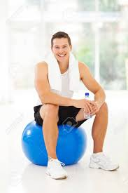 cheerful young man sitting on gym ball holding water bottle stock photo 22538233