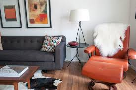 dallas burnt orange sofa with wooden tripod table lamps living room midcentury and cowhide rug round