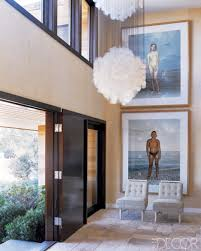 joe nahem and tom fox for this beach house foyer had the interesting chandelier and two over sized pieces of art become the focal points in this dramatic