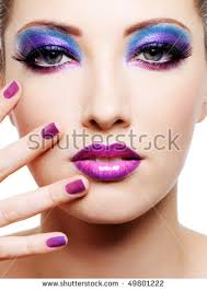 beautiful young female face with bright fashion multicolored make up and beauty purple manicure of