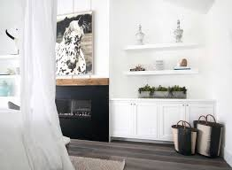 bed accented with white sheers facing a black fireplace lined with a wood mantle under a black and white horse art flanked by stacked floating shelves