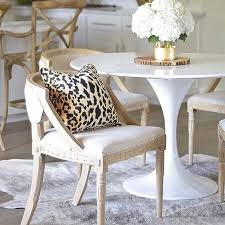 a neutral and chic dining space with a cheetah print pillow and a cow skin rug