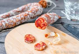 homemade chorizo that has further dried being sliced on a cutting board