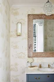 beautiful cream toile wallpaper covers the walls of this lovely powder room featuring a blue bath vanity accented with brass pulls and a honed white marble