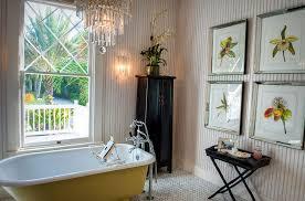 beach cottage bathroom with yellow claw foot bathtub and a chandelier design gh3