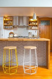 a stylish bar counter clad with geo tiles that echo with the backsplash and wood with