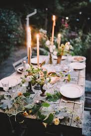 A beautiful outdoor dining table. Rustic wooden table with plant table  decorations and tall candles.