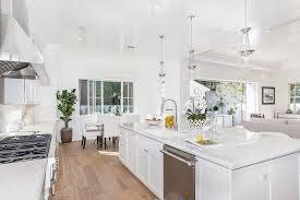 kitchen with maple hardwood flooring and white cabinets with marble countertops