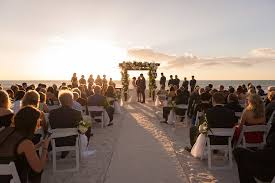 clearwater beach wedding ceremony portrait with white folding chairs decorated with white and greenery fl bouquets with tulle ceremony arch with white