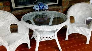 furniture round glass top table on white wicker frame and legs plus white wicker chairs