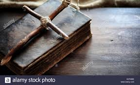 religious old book on a wooden table a religious cross tied wit