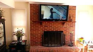 brick installation above mantel over the fireplace on 2 tv install