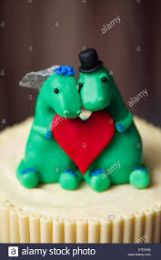 Dinosaur Bride And Groom Cake Toppers On A Wedding Cake Stock Photo
