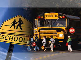 Students crossing to load on a school bus