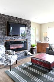black ledgestone fireplace surround with reclaimed wood around mounted tv unique coffee table trunk and home decor kylie m interiors e design vancouver