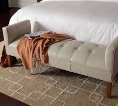 White leather end bed bench with higher armrests and wooden base