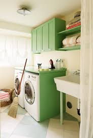 lovely laundry room features kelly green cabinets adorned with cup pulls suspended over an enclosed washer and dryer under green countertop beside a utility