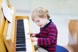 hobbies for kids. two years old toddler boy playing piano, music schoool. hobbies for kids