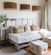 farmhouse daybed made of pallets with an old door for a backboard love the poufs in front of it