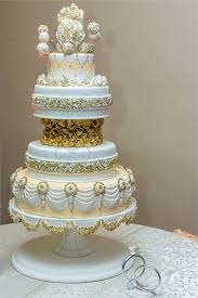 multi tiered and shaped wedding cake with gold features