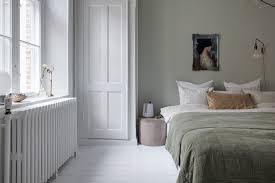 i think the pale green and beige color palette works great in this bedroom the walls have a very subtile green grey color which makes the white doors and