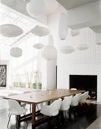 12 nelson bubble suspension lights in diffe shapes and sizes hang over a modern dining room table with white saarinen arm chairs and sid
