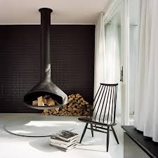 in this modern living room a hanging fireplace matches the black tile accent wall and