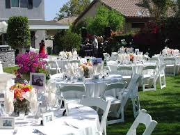 bakcyard party decorations in white wooden chairs and round table with white table clothes also sweet flowers over green grass yard