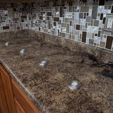 under cabinet lighting pucks laid across countertop with power cord close to
