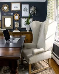 dramatic dark walls in this home office with large desk and wing back chair kellyelko
