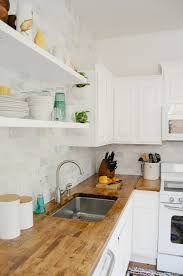 like the open shelving and warm wood countertop countertop to ceiling marble tile with open shelving and butcher block countertops