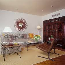 living rooms sectional sofa woven sisal area rug antique carved colonial armoire barcelona chair red sunburst