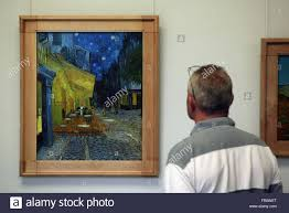 visitor looks at the painting cafe terrace at night 1888 by vincent van gogh in the kroller muller museum in otterlo netherlands