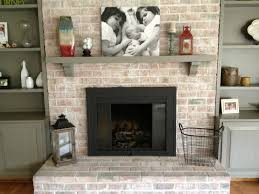 interior beige brick fireplace with rectangle black metal firebox and grey wooden mantel shelf on