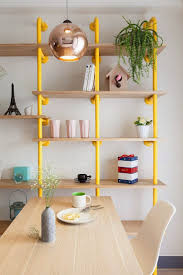 Modern shelving with yellow pipe brackets. Colorful but industrial, great  inspiration for DIY bookcase // The Wonderland Apartment by House Design