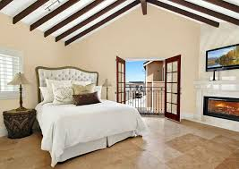 mediterranean master bedroom with fireplace arched ceiling and outdoor balcony views