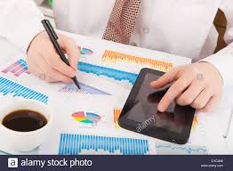 Businessman In White Shirt Analyzing Graphs And Charts Stock