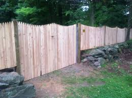 Scalloped cedar stockade fence with double gate and round pressure treated  posts