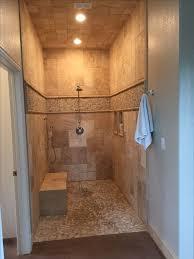 Walk in shower, no door, travertine and pebble tile.