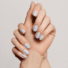 person s hands painted with pale blue fingernails on an off white background