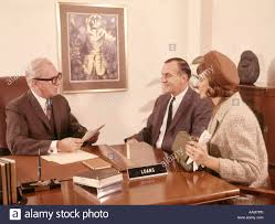 1960 1960s man interviewing couple man woman at desk bank loan officer mortgage finance office interview banking