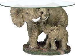 Carved from high quality acacia wood, this coffee table chest features richly carved images of endangered thai elephants roaming through the forest, sure to add beauty and grace to any room. Amazon Com Design Toscano Elephants Majesty African Decor Coffee Table With Glass Top 30 Inch Polyresin Full Color Furniture Decor