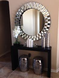 Glamorous hallway with coffe coloured walls and large round silver mirror.