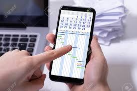 Gantt Chart Mobile Close Up Of A Persons Hand Analyzing Gantt Chart On Cellphone